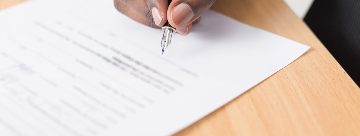 Image of a person signing a document
