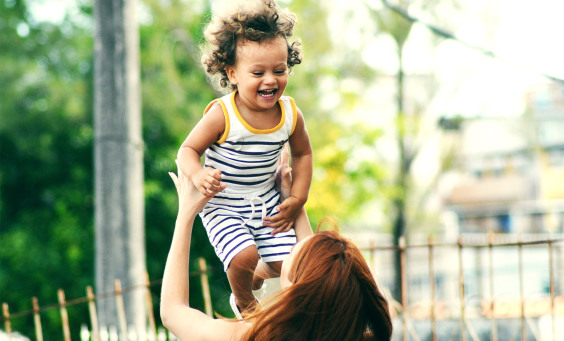 A young girl with curly hair laughing as her brunette mom throws her in the air