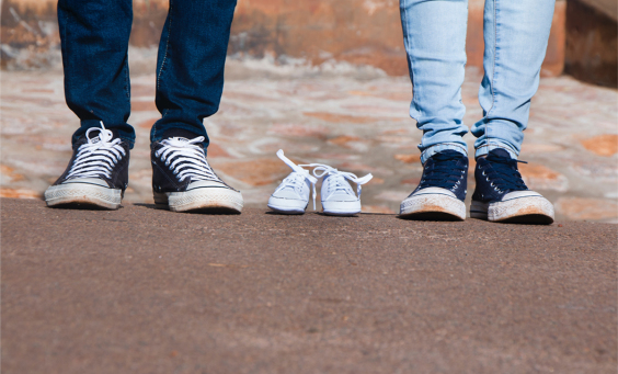 Image of a pair of gray low-top shoes between two persons wearing jeans