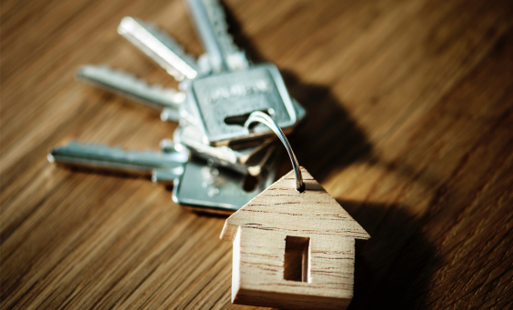 Picture of a key chain in the shape of a house with a few keys attached to it