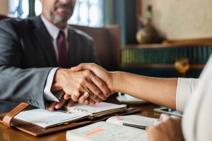 Image of an attorney and client shaking hands
