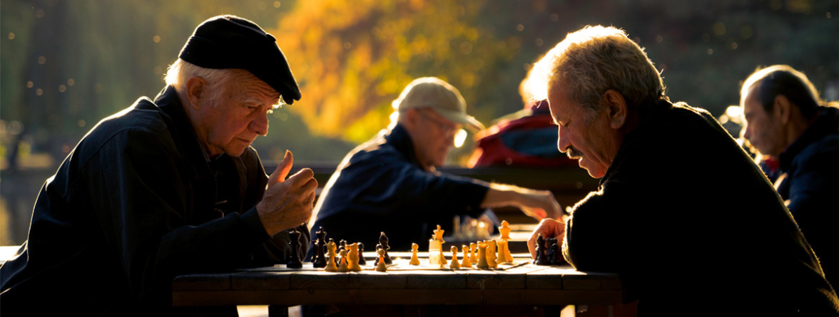Image of two LGBT elders playing a game of chess