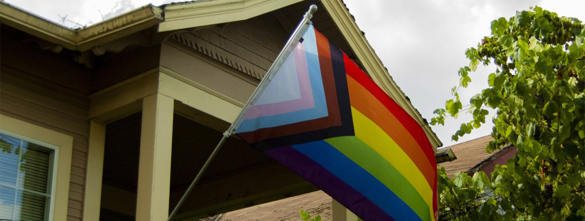 The LGBT flag hanging in front of a house